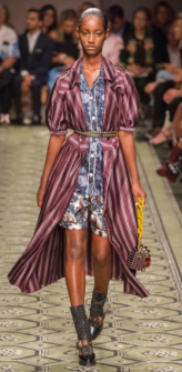 BURBERRY The draping flowing overcoat sets a light tone to a heavy design. The thick yellow chain-strapped bag and beaded belt combined with the gray high socks and chunky sandals strengthens the warmth of the style.