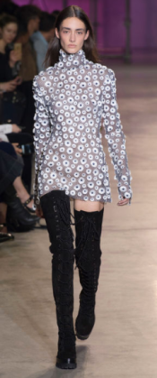 ELLERY Rebellious, all black, lace up over-the-knee boots contrast the long-sleeved flower-like patterned dress creating a shift in weight throughout the design.