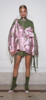 FENTY X PUMA The edgy olive green shortly-hemmed dress is layered with a metallic pink jacket drawing attention away from the edginess of the design.