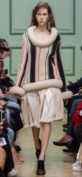 J.W. ANDERSON The striped sweater with thick cuffs and an exaggerated rollneck mimics the Elizabethan neck ruffle. The neutral skirt is a compilation of layers with a fringe lining.