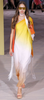 TEMPERLEY LONDON The use of bright colors encourages the warm tone of the lightly weighed design and the dangling fringe sets a balance for the one shoulder dress.